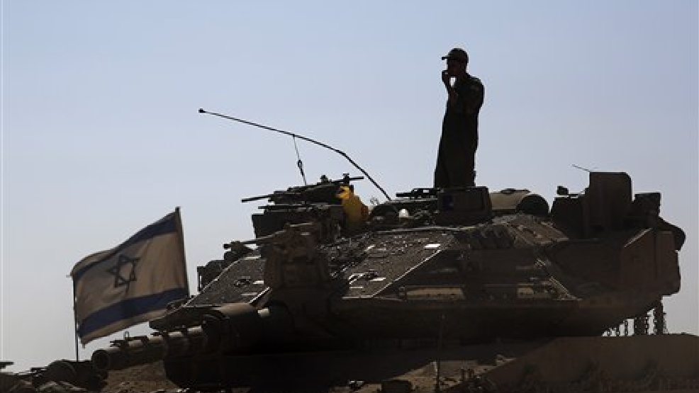 An Israeli soldier standing on top of a tank in a staging area near the Israel Gaza border, Saturday, August 2, 2014. (AP Photo/Tsafrir Abayov)