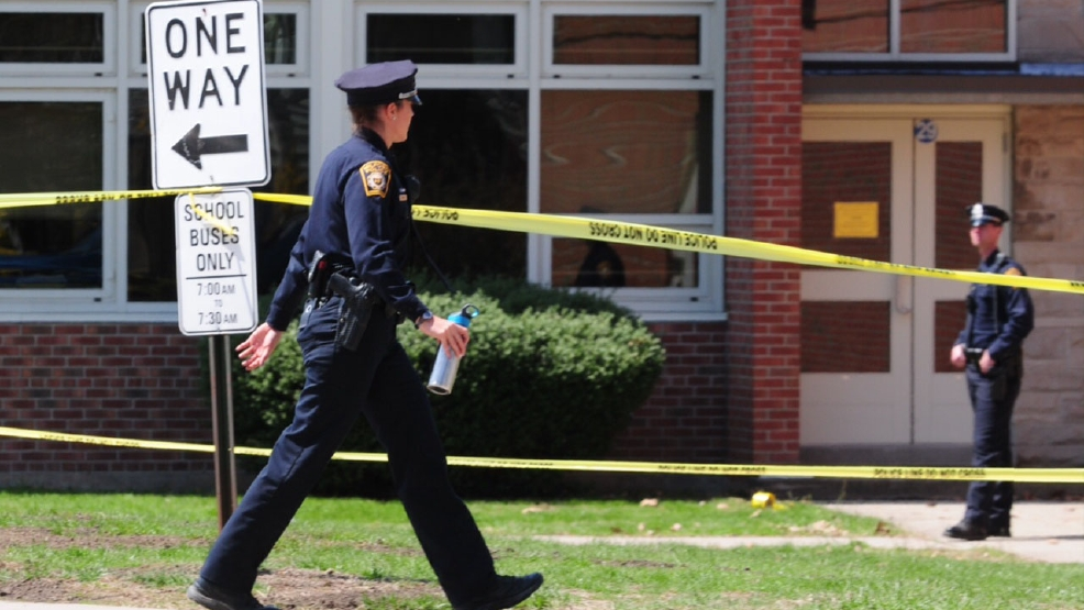Police remain on scene at Jonathan Law High School where a 16-year-old girl was stabbed to death in Milford, Conn., Friday, April 25, 2014. A teenage boy is in custody, and police are investigating whether the attack stemmed from her turning down an invitation to be his prom date. (AP Photo/The New Haven Register, Peter Hvizdak)