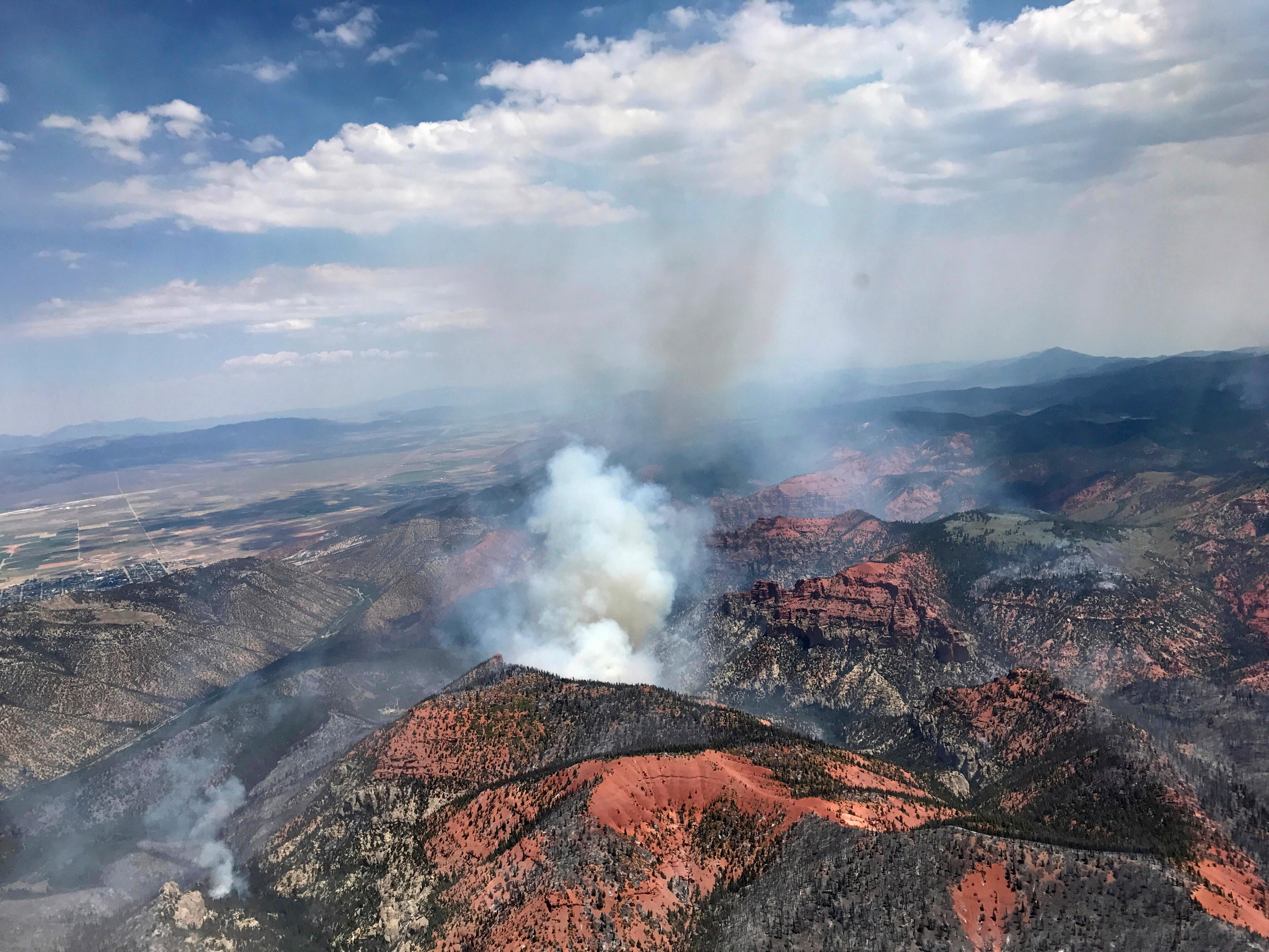 This Monday, June 26, 2017, photo provided by the Utah Governor's Office, shows fire activity near Parowan, during a tour by Utah Lt. Gov. Spencer Cox, in southern Utah. The nation's largest wildfire has forced more than 1,500 people from their homes and cabins in a southern Utah mountain area home to a ski town and popular fishing lake. (Justin Harding/Utah Governor's Office via AP)