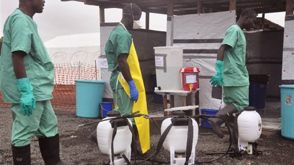Health workers prepare disinfectant in containers, foreground, to spray at an Ebola treatment center in the city of Monrovia, Liberia, Monday, Aug. 18, 2014. Liberia's armed forces were given orders to shoot people trying to illegally cross the border from neighboring Sierra Leone, which was closed to stem the spread of Ebola, local newspaper Daily Observer reported Monday. (AP Photo/Abbas Dulleh)