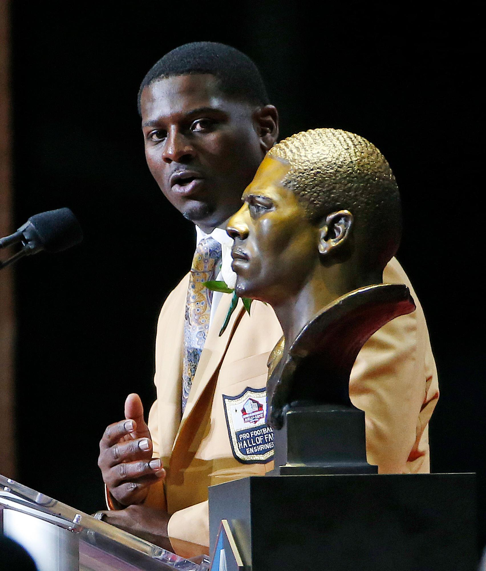 LaDainian Tomlinson speaks next to a bust of him at the Pro Football Hall of Fame inductions Saturday, Aug. 5, 2017, in Canton, Ohio. (AP Photo/Ron Schwane)