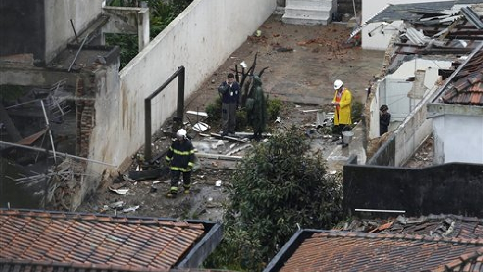 Officials work at the crash site of a small plane that was carrying Brazilian presidential candidate Eduardo Campos and several campaign officials, in the port city of Santos, Brazil, Wednesday, Aug. 13, 2014. All seven people aboard the plane, including a campaign photographer and press advisor, as well as two pilots, died in the crash, City Hall press officer Patricia Fagueiro confirmed. (AP Photo/Nelson Antoine)