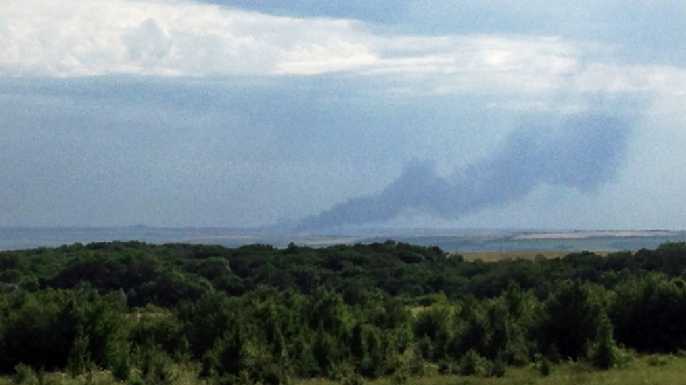 In this photo taken with a mobile phone provided by Andrei Kashtanov, smoke rises from where a Malaysia Airlines commercial plane crashed in eastern Ukraine, Thursday, July 17, 2014. Malaysia Airlines has said 295 people were aboard the flight from Amsterdam to Kuala Lumpur. (AP Photo/Andrei Kashtanov)