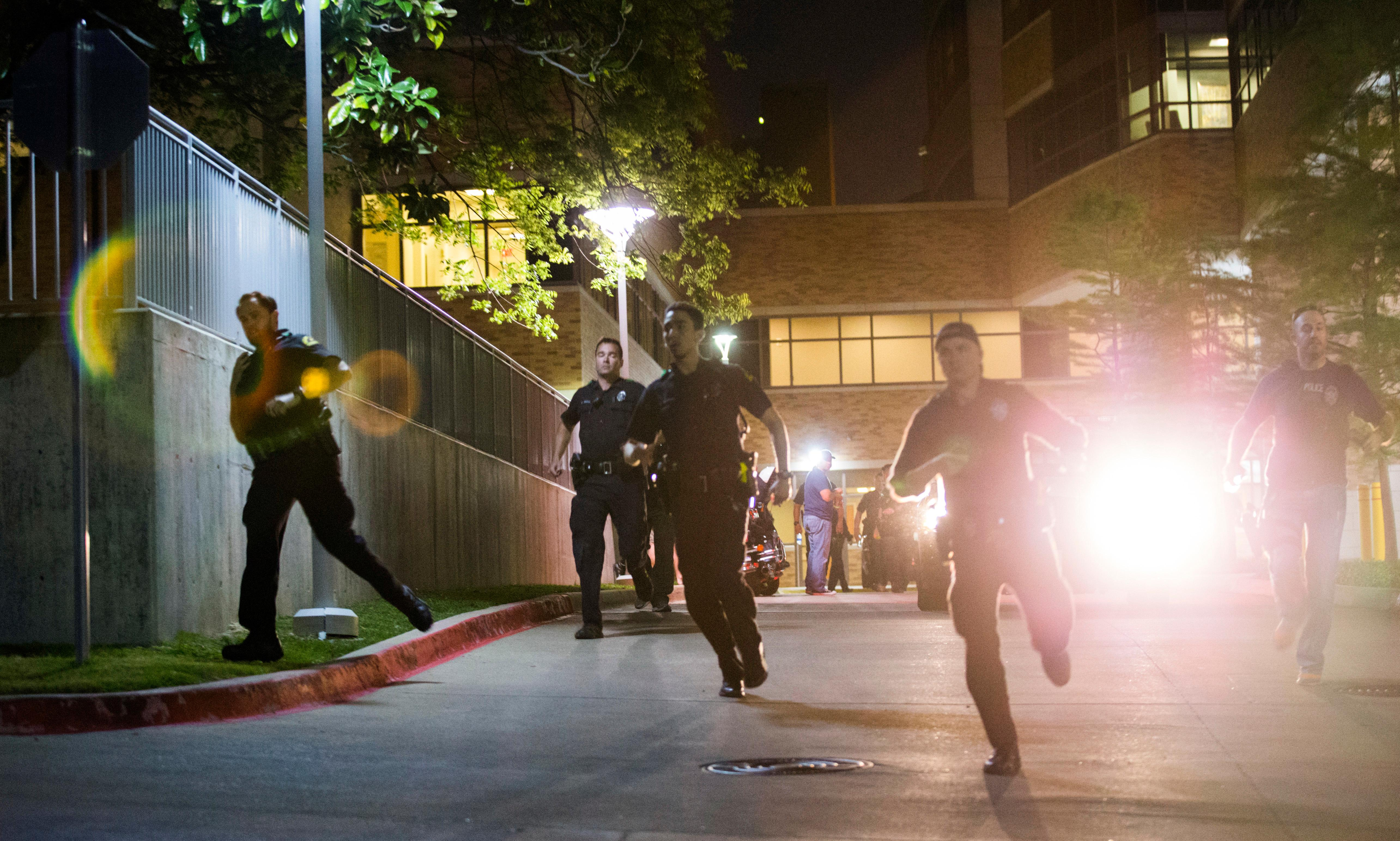 Police officers run away from the emergency room to their cars at Texas Health Presbyterian Hospital Dallas after a man shot two officers outside a Home Depot on Tuesday, April 24, 2018, in Dallas. (Ashley Landis/The Dallas Morning News via AP)