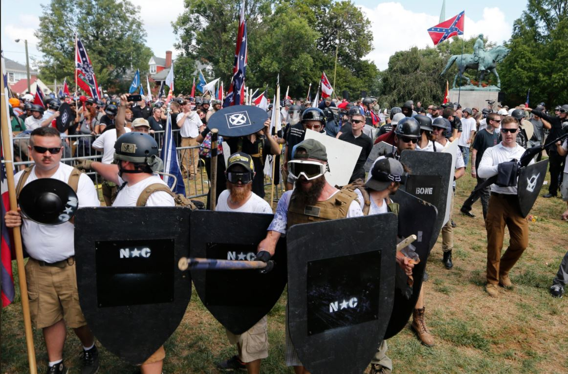 White nationalist demonstrators hold their ground as they clash with counter demonstrators in Lee Park in Charlottesville, Va., Saturday, Aug. 12, 2017. Hundreds of people chanted, threw punches, hurled water bottles and unleashed chemical sprays on each other Saturday after violence erupted at a white nationalist rally in Virginia. At least one person was arrested. (AP Photo/Steve Helber)