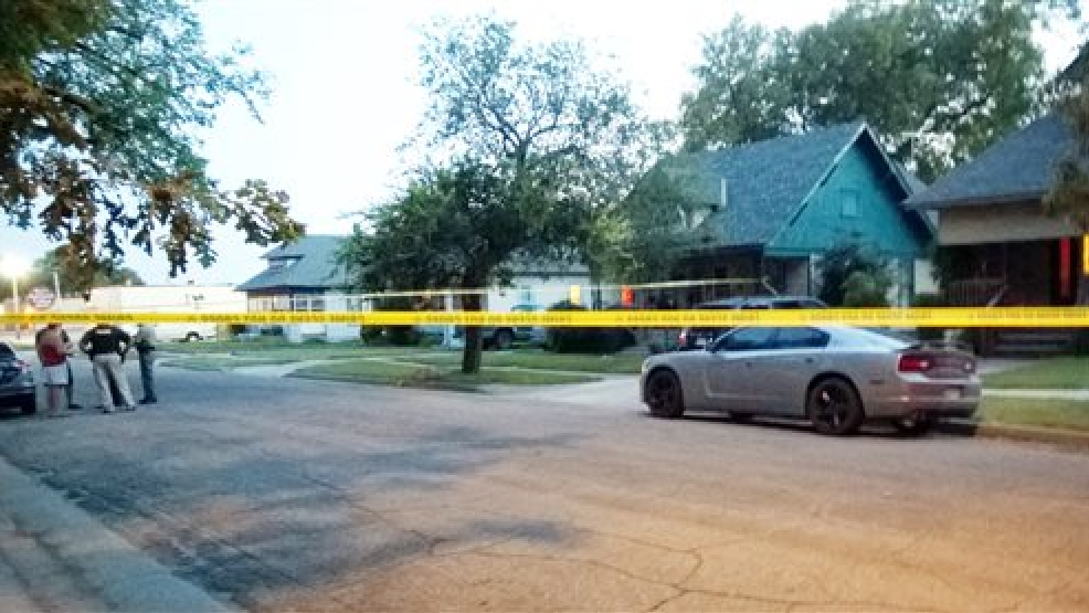 "In this Thursday, July 24, 2014 photo police tape surrounds a gray car outside a Wichita, Kan., where a 10-month-old girl died after being left inside a hot car. Authorities said Friday they have arrested the girl's foster parent on suspicion of aggravated endangerment but charges have not been filed. Police said the man had ""somehow forgotten"" leaving the girl in the back seat after picking her up from the baby sitter late Thursday afternoon. (AP Photo/The Wichita Eagle, Matt Riedl)"