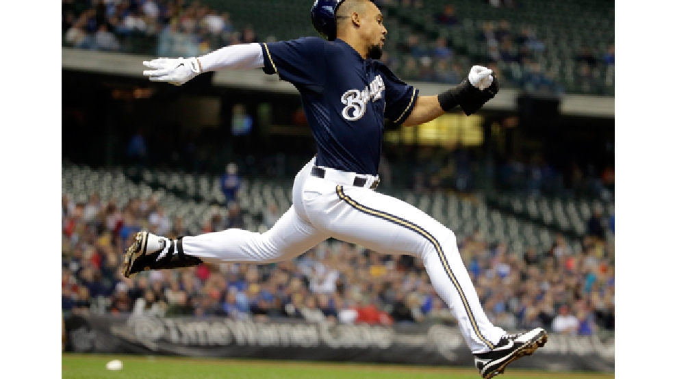 Milwaukee Brewers' Carlos Gomez loses his helmet as he races to first on a bunt during the sixth inning of a baseball game against the Arizona Diamondbacks Wednesday, May 7, 2014, in Milwaukee. Gomez beat the throw. (AP Photo/Morry Gash)