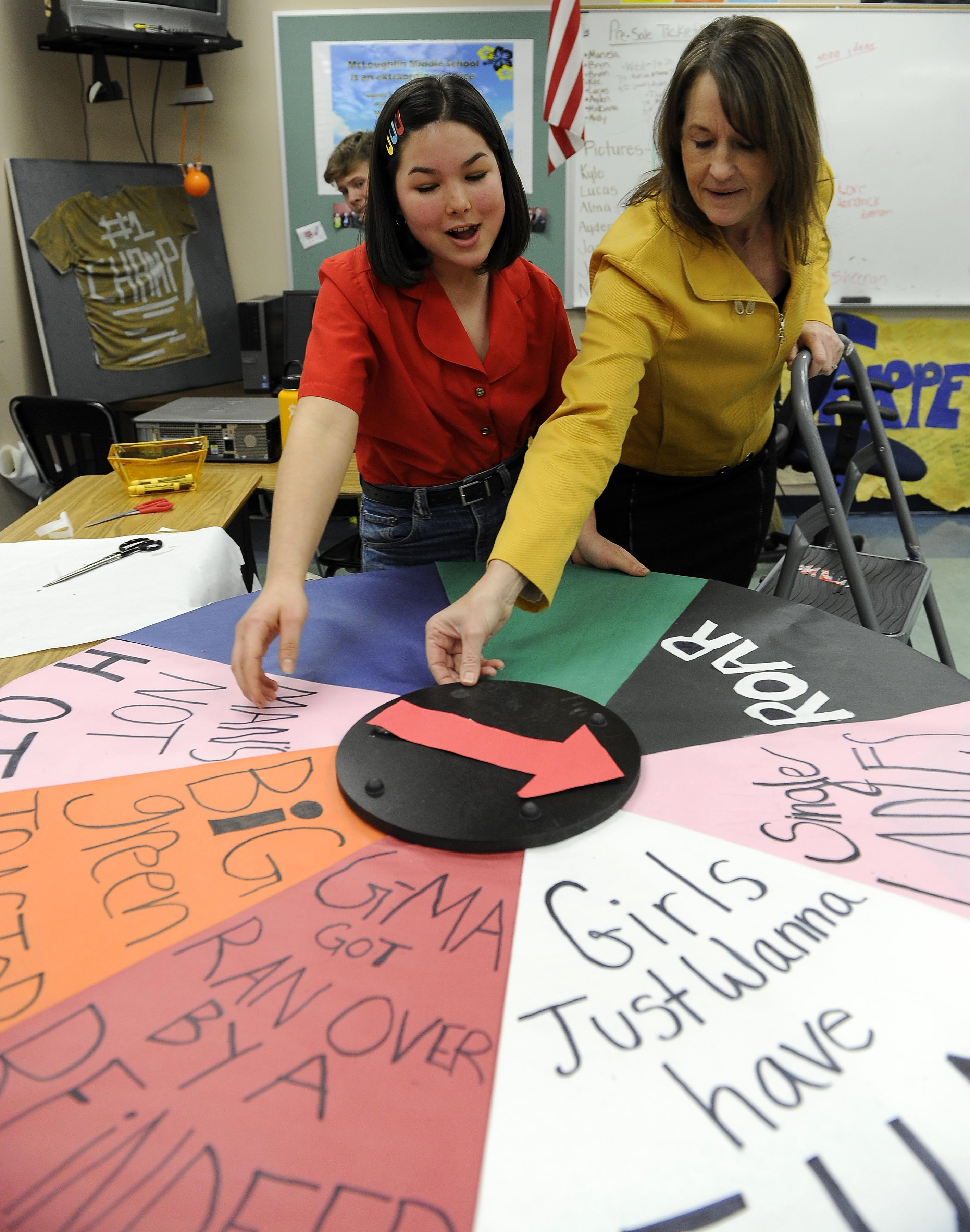 Eighth-grade student Ayden Yriarte and McLoughlin Middle School Principal Linda White work on a game wheel for an upcoming school dance. [Mail Tribune / Andy Atkinson]