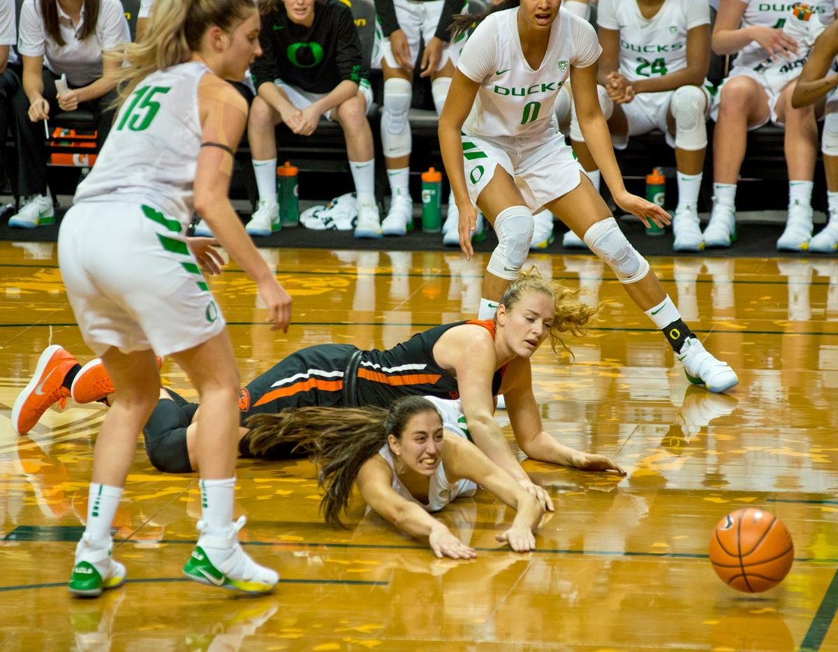 Oregon Ducks Maite Carzorla (#5, white jersey) and Oregon State Beavers Marie Gulich (#21) fight for a loose ball. The Oregon Ducks defeated the Oregon State Beavers 75-63 on Sunday afternoon in front of a crowd of 7,249 at Matthew Knight Arena. The Ducks and Beavers split the two game Civil War with the Beavers defeating the Ducks on Friday night in Corvallis. The Ducks had four players in double digits: Satou Sabally with 21 points, Maite Cazorla with 16, Sabrina Ionescu with 15, and Mallory McGwire with 14. The Ducks shot 48.4% from the floor compared to the Beavers 37.3%. The Ducks are now 7-1 in conference play. Photo by Dan Morrison, Oregon News Lab