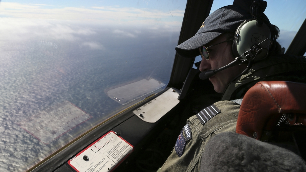 Royal New Zealand Air Force P-3 Orion's captain, Wing Comdr. Rob Shearer watches out of the window of his aircraft while searching for the missing Malaysia Airlines Flight MH370 in the southern Indian Ocean, Monday, March 31, 2014. (AP Photo/Rob Griffith, Pool)
