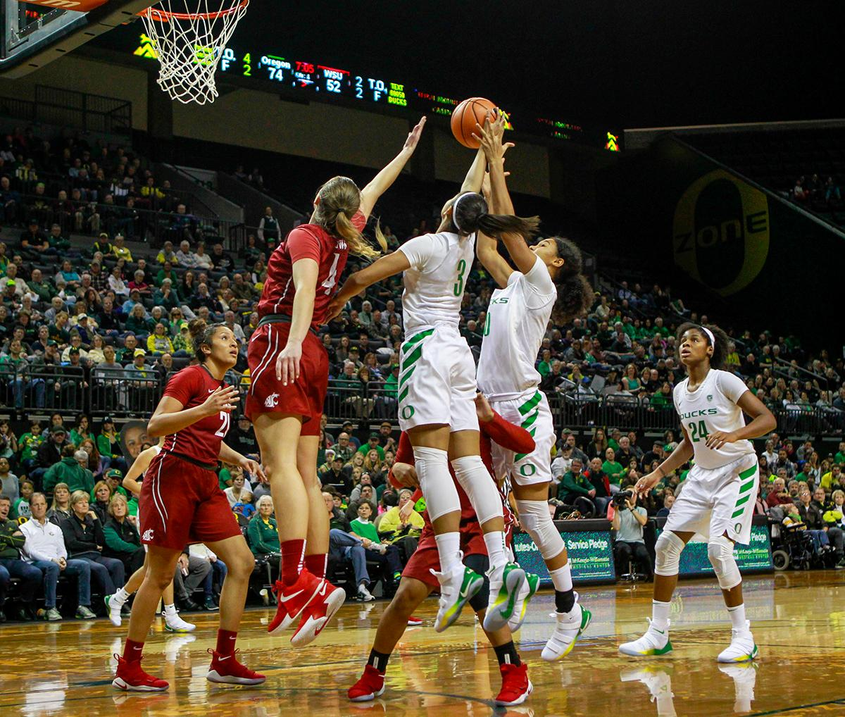 The Oregon Ducks and Washington State University Cougars go up for control of a rebound. In their first conference basketball game of the season, the Oregon Women Ducks defeated the Washington State Cougars 89-56 in Matt Knight Arena Saturday afternoon. Oregon's Ruthy Hebard ran up 25 points with 10 rebounds. Sabrina Ionescu shot 25 points with five three-pointers and three rebounds. Lexi Bando added 18 points, with four three-pointers and pulled down three rebounds. Satou Sabally ended the game with 14 points with one three-pointer and two rebounds. The Ducks are now 12-2 overall with 1-0 in conference and the Cougars stand at 7-6 overall and 0-1 in conference play. The Oregon Women Ducks next play the University of Washington Huskies at 1:00 pm on Sunday. Photo by Rhianna Gelhart, Oregon News Lab