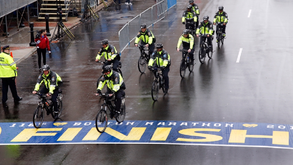 Police on bikes cycle across the Boston Marathon finish line prior to a remembrance ceremony for family members and survivors of the 2013 Boston Marathon bombing on Boylston Street in Boston, Tuesday, April 15, 2014. (AP Photo/Elise Amendola)