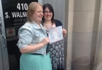 Natalie, left, and Heather Starr pose in front of the Outagamie County Administration Building in Appleton with their marriage license June 9, 2014. The Starrs were the first same-sex couple to be legally married in Outagamie County. (WLUK/Bill Miston)