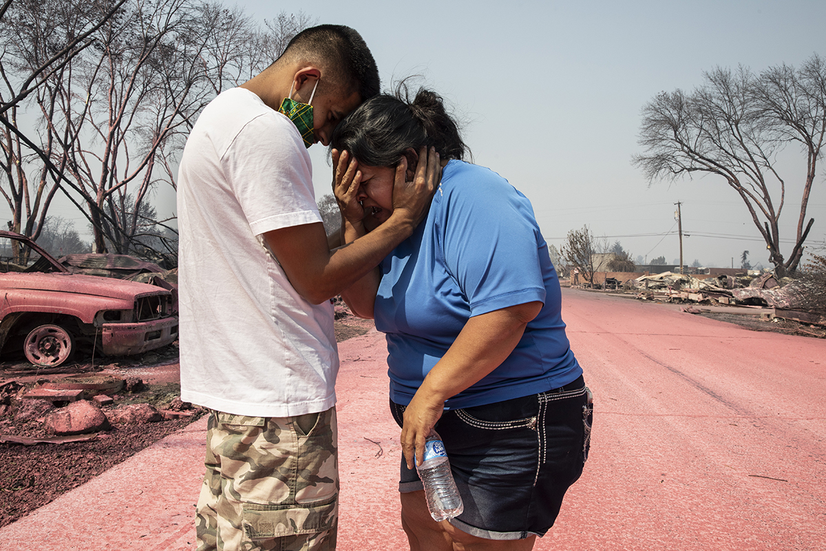 Dora Negrete is consoled consoled by her son Hector Rocha after seeing their destroyed mobile home at the Talent Mobile Estates, Thursday, Sept. 10, 2020, in Talent, Ore., after wildfires devastates the region. (AP Photo/Paula Bronstein)