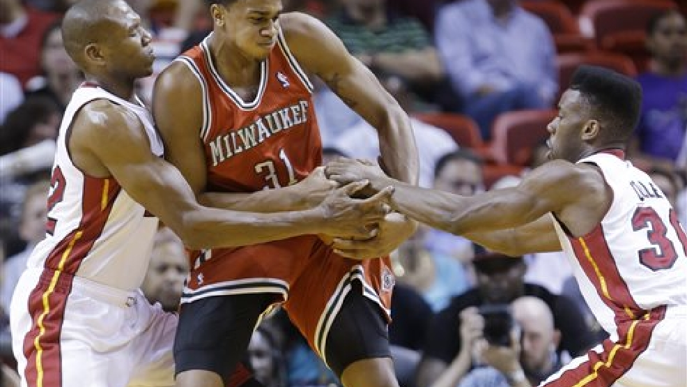 Milwaukee Bucks center John Henson (31) tries to regain control of the ball from Miami Heat forward James Jones (22) and guard Norris Cole (30) during the first half of an NBA basketball game on Wednesday, April 2, 2014, in Miami. (AP Photo/Wilfredo Lee)