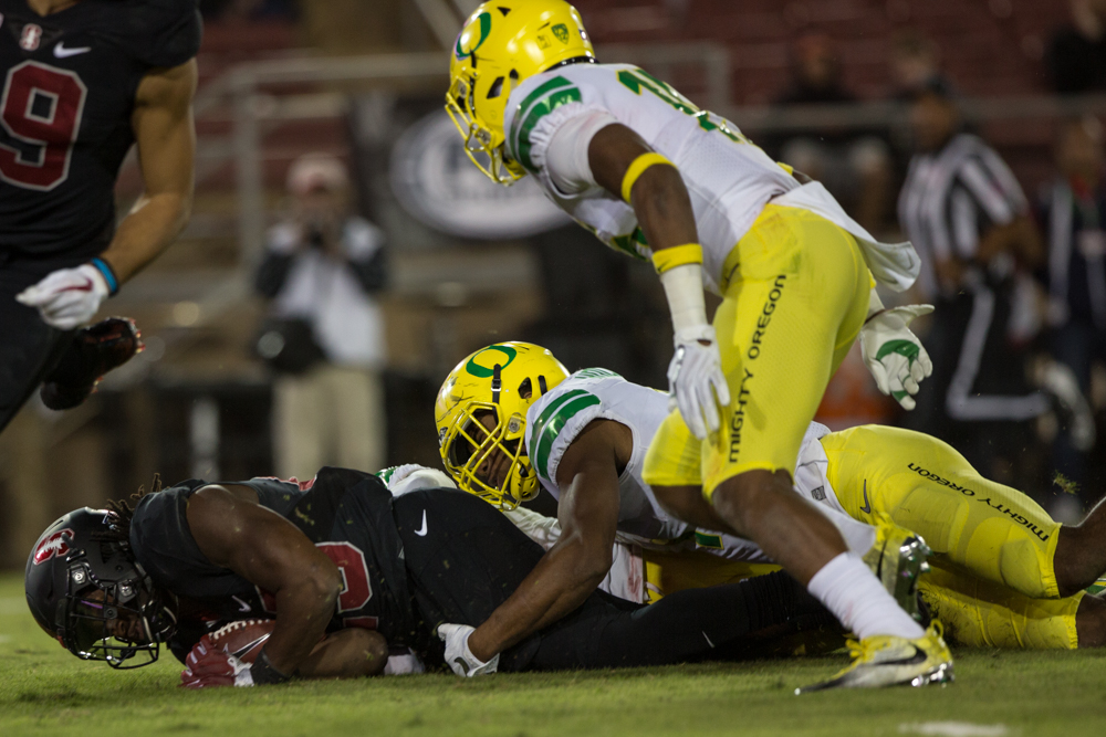 Stanford runningback Trevor Speights (#23) is dragged down by an Oregon defender.  The Oregon Ducks fell to the Stanford Cardinal 49-7 at Stanford Stadium, bringing their record to 4-3 for the season.  Photo by Austin Hicks, Oregon News Lab