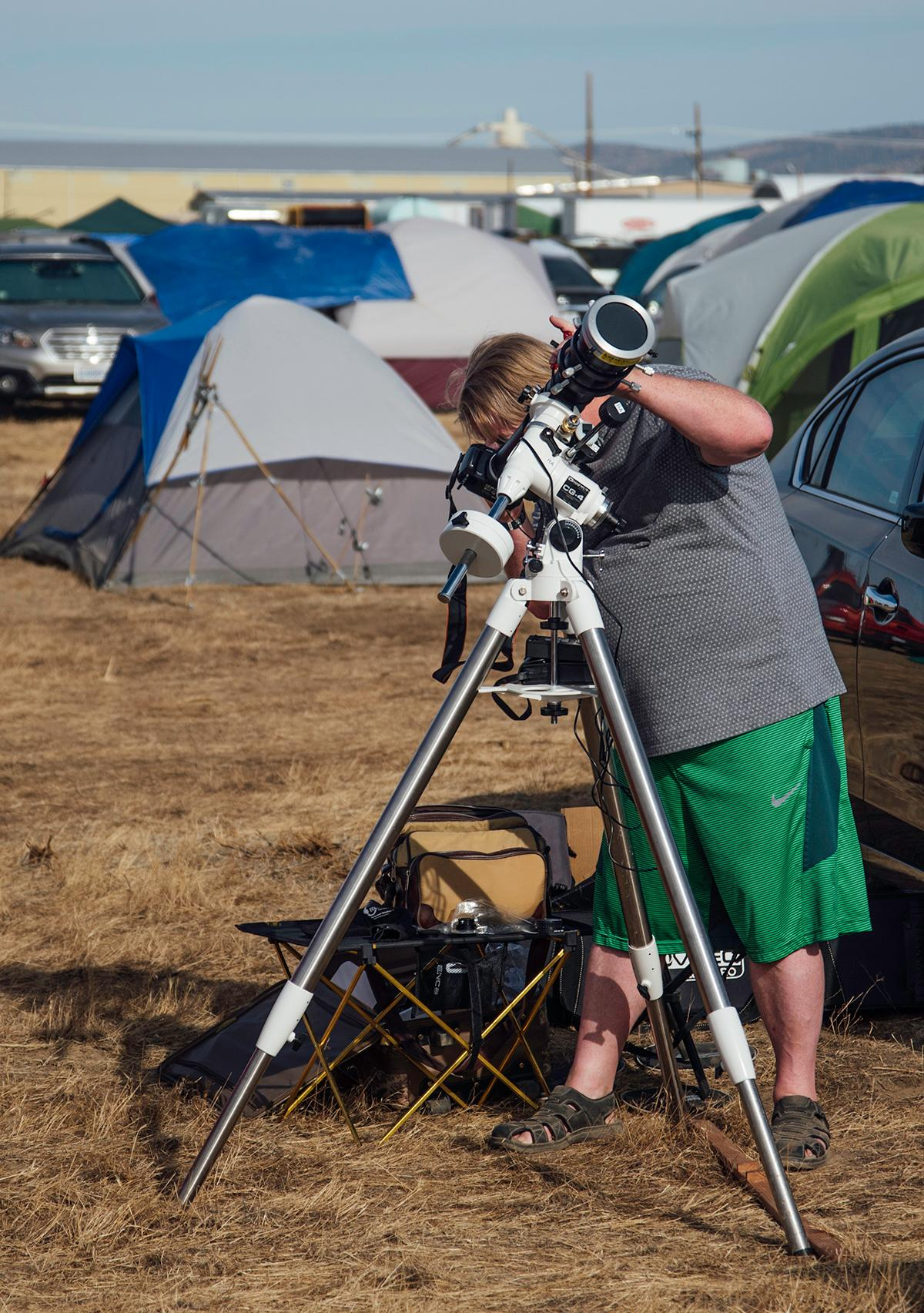 A camper looks through his telescope at the setting sun to test out his solar filter at Solar Port, the makeshift campground in Madras, Oregon. Photo by Cheyenne Thorpe, Oregon News Lab