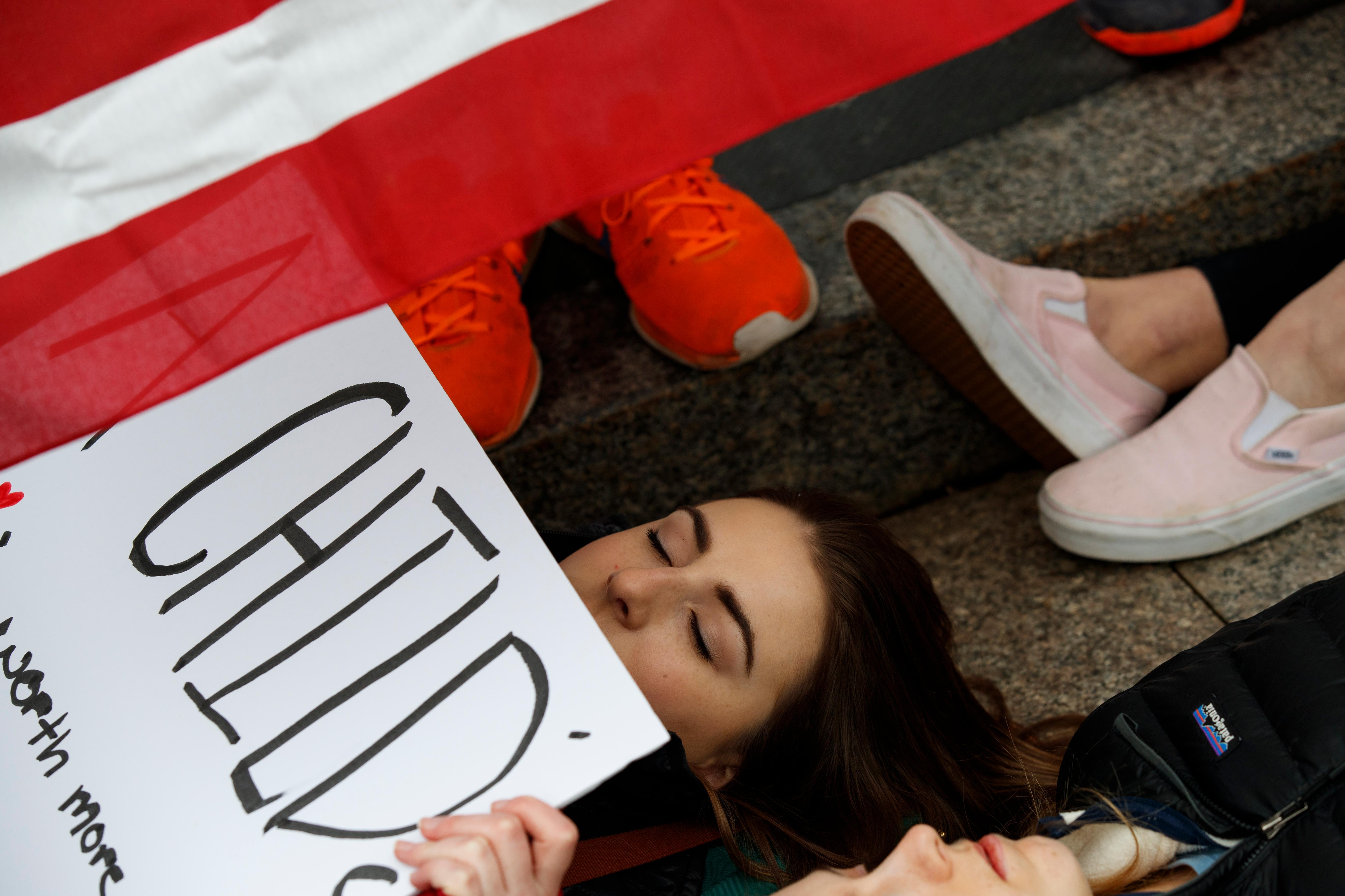 "Anna Hurley, 15, of Washington, top, and other demonstrators participate in a ""lie-in"" during a protest in favor of gun control reform in front of the White House, Monday, Feb. 19, 2018, in Washington. (AP Photo/Evan Vucci)"