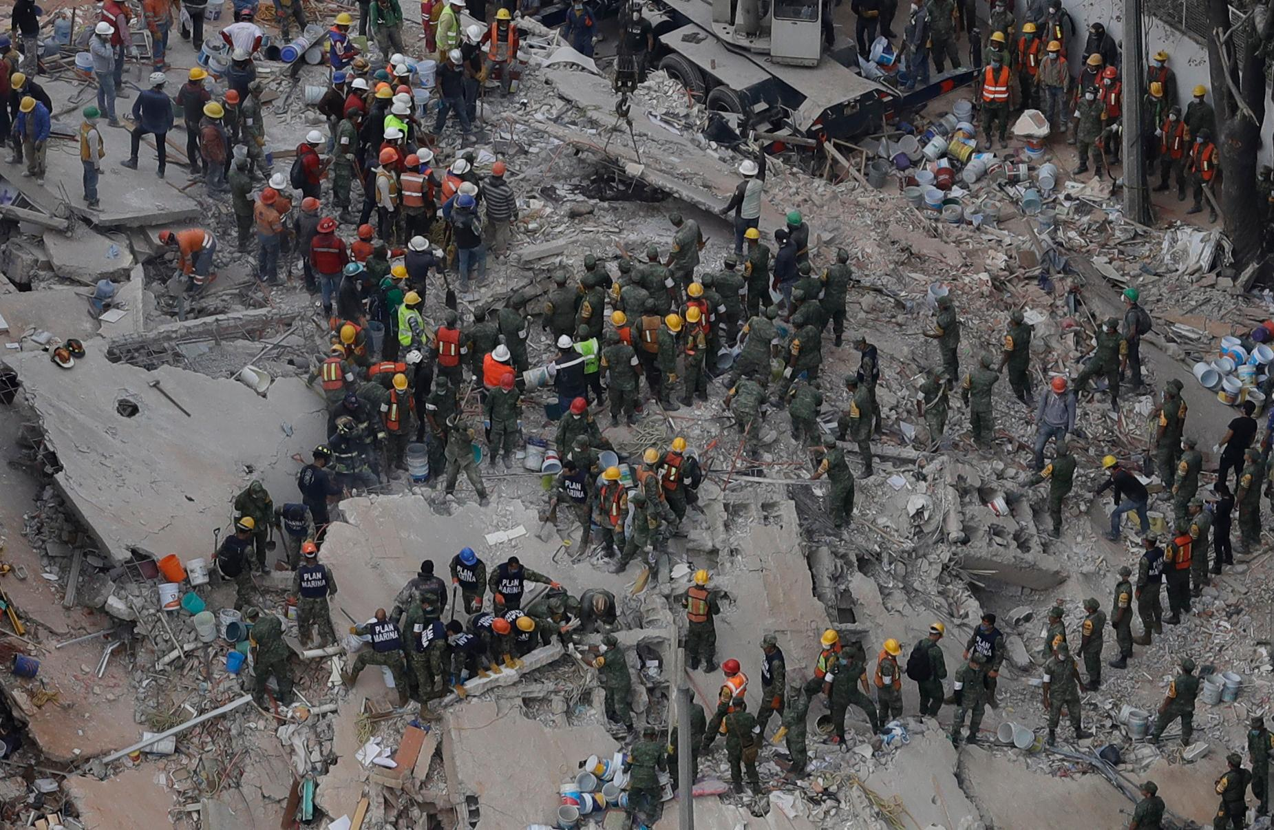 Rescue workers remove rubble as they search for people trapped inside a collapsed building in the Del Valle area of Mexico City, Wednesday, Sept. 20, 2017. Mexicans across the city are digging through collapsed buildings, trying to save people trapped in debris under schools, homes and businesses, toppled by a 7.1 earthquake that killed more than 200 people. (AP Photo/Rebecca Blackwell)