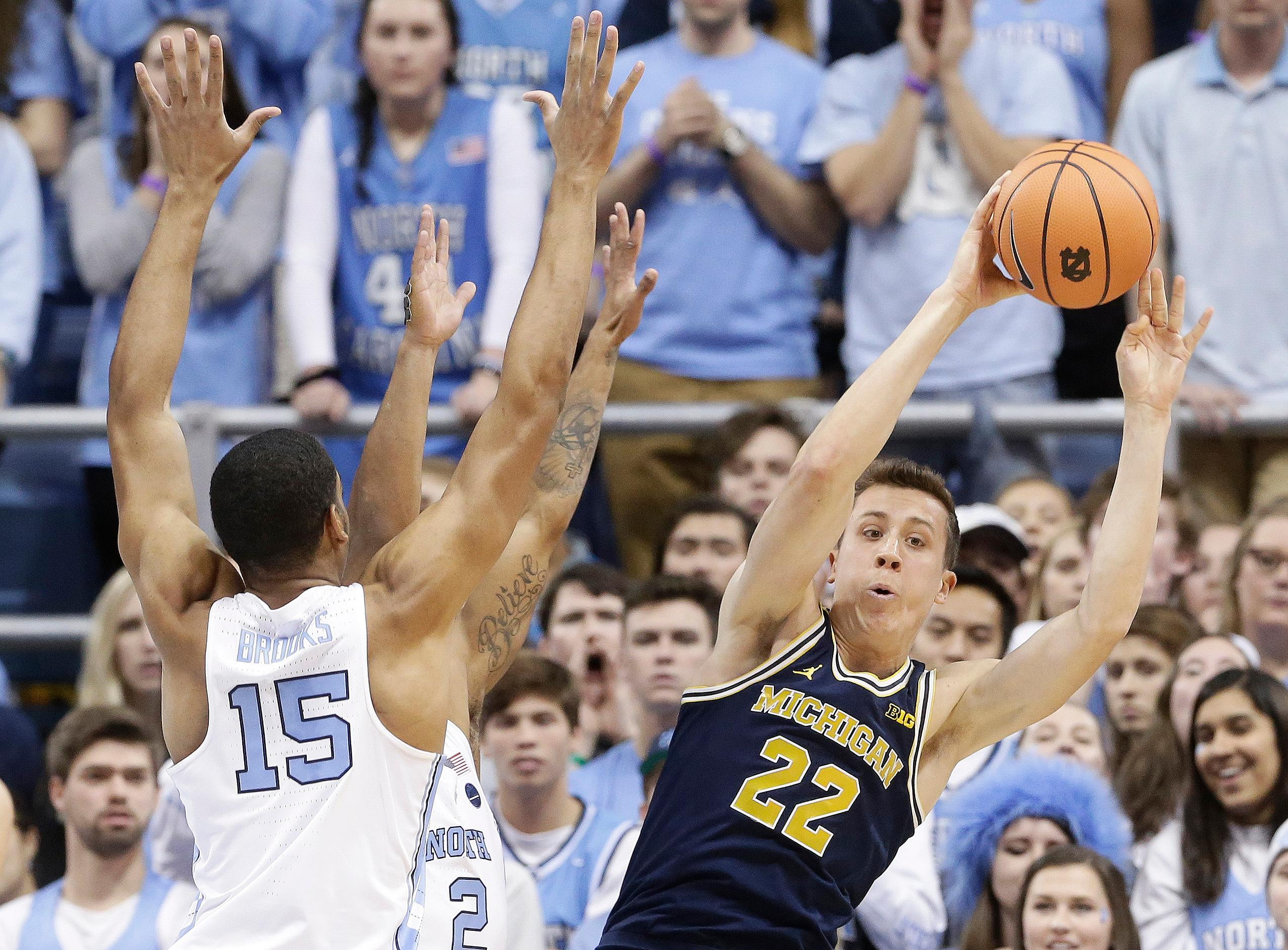 North Carolina's Garrison Brooks (15) defends while Michigan's Duncan Robinson (22) looks to pass during the first half of an NCAA college basketball game in Chapel Hill, N.C., Wednesday, Nov. 29, 2017. (AP Photo/Gerry Broome)