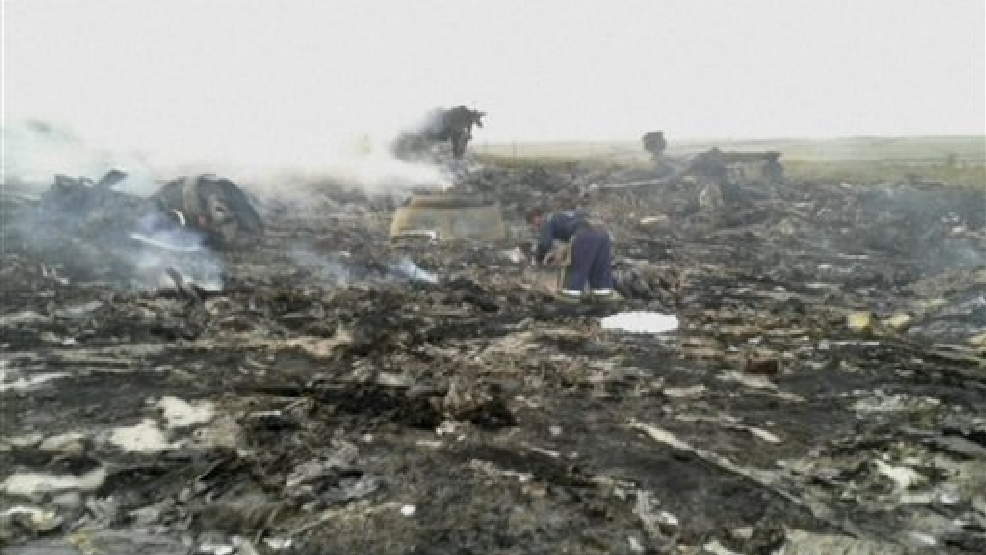 In this image taken from video, Thursday July 17, 2014, people walk amongst the debris at the crash site after a passenger plane carrying 295 people was shot down Thursday as it flew over Ukraine, near the village of Hrabove, in eastern Ukraine. Malaysia Airlines tweeted that it lost contact with one of its flights as it was traveling from Amsterdam to Kuala Lumpur over Ukrainian airspace. (AP Photo / Channel 1)