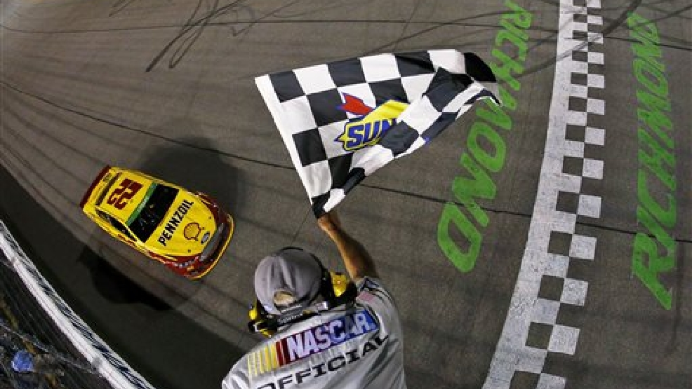 In a photo provided by NASCAR, Joey Logano takes the checkered flag to win the NASCAR Sprint Cup Series auto race at Richmond International Raceway on Saturday, April 26, 2014, in Richmond, Va.  (AP Photo/NASCAR, Jeff Zelevansky)