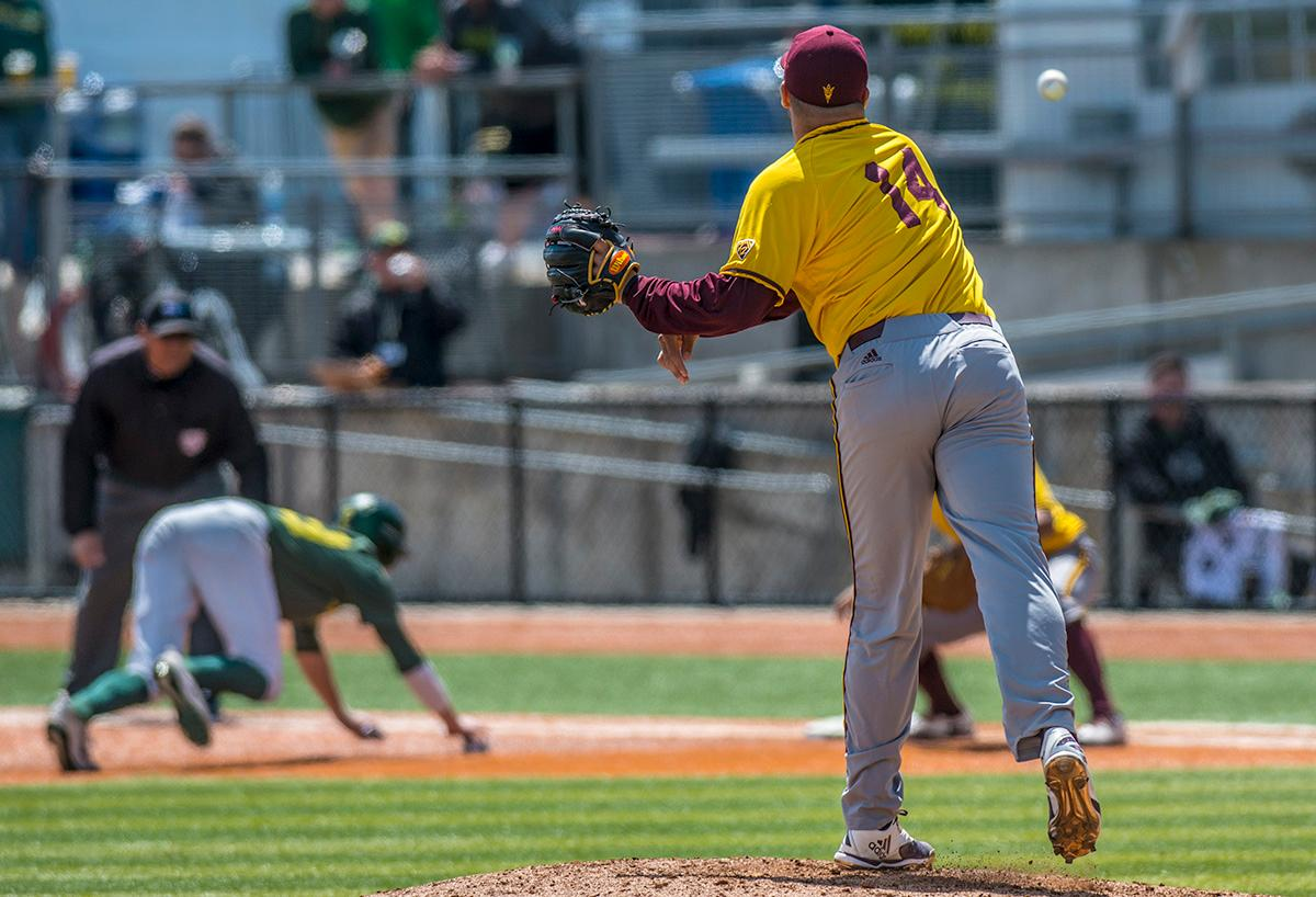 Arizona State Sun Devils right-handed pitcher Jake Godfrey (#14) checks first base to attempt to get an Oregon Ducks player out. The Oregon Ducks defeated the Arizona State Sun Devils 3-2 on Sunday in the final game of the three-game series to close out with two wins and one loss. Jacob Bennett (#16) gave the Ducks their first point in the third inning. Kyle Kasser (#9) and Morgan McCullough (#1) added two more points in the fourth inning to give the Oregon Ducks enough of a lead to hold off the Sun Devils to the end of the ninth. The Oregon Ducks will play the Oregon State Beavers next in Corvallis, Ore, on May 2 at 5:30 p.m. Photo by Rhianna Gelhart, Oregon News Lab