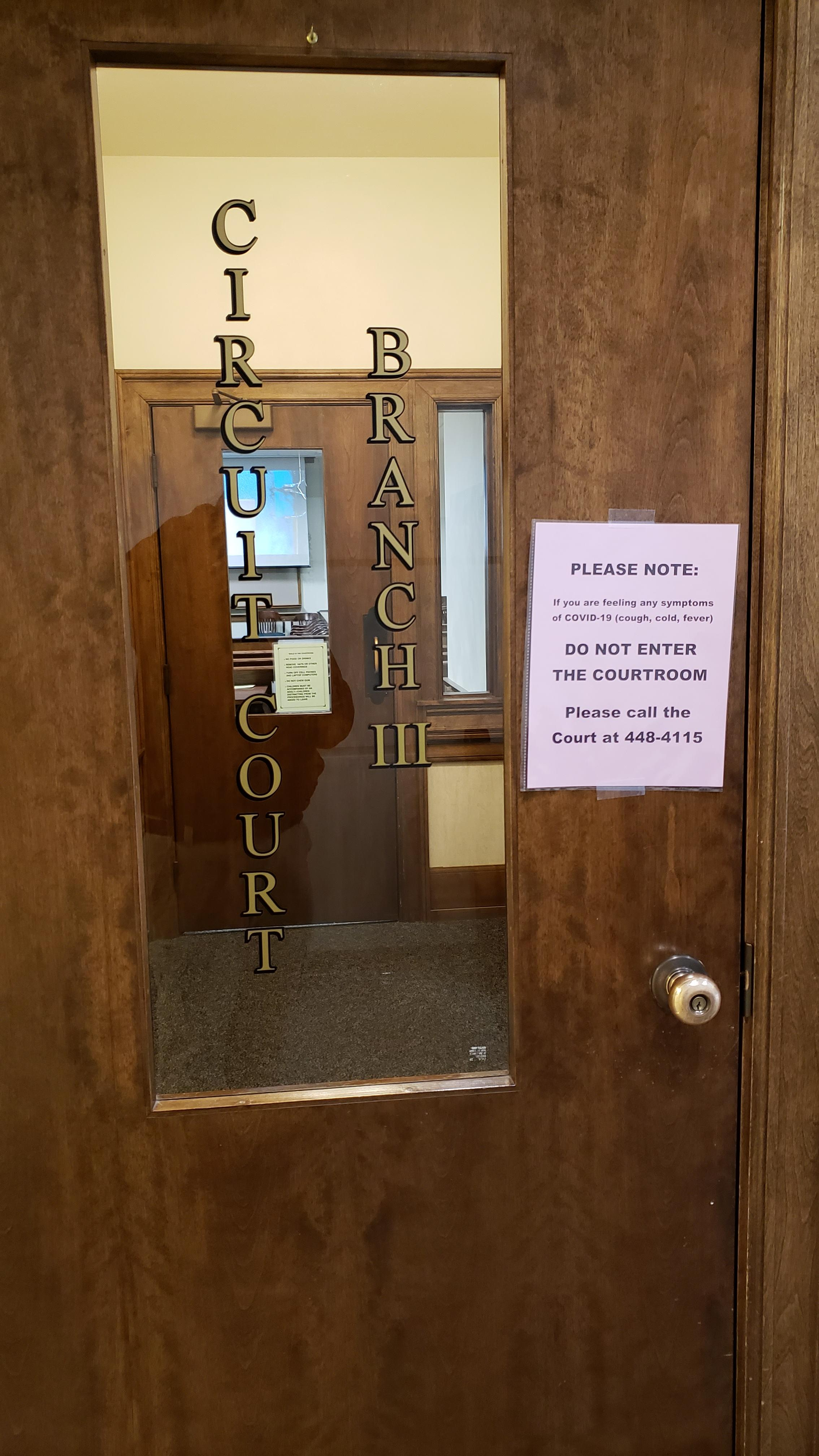 A sign outside a Brown County, Wisconsin, courtroom March 20, 2020, advises people who are feeling sick with coronavirus symptoms not to enter the room. (WLUK/Don Steffens)