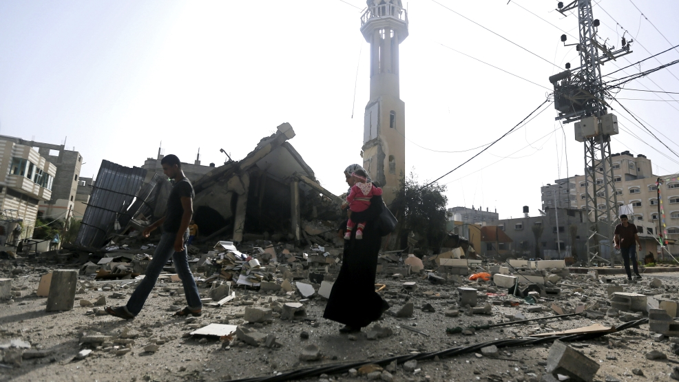 Palestinians walk past the ruins of the Al-Tawfeeq mosque after it was hit by an Israeli missile strike in the Nuseirat refugee camp, central Gaza Strip, Saturday, July 12, 2014. Palestinian officials said Israeli airstrikes targeting Hamas in Gaza hit a mosque and a center for the disabled where two women were killed Saturday, raising the Palestinian death toll from the offensive to more than 120, that showed no signs of slowing down. (AP Photo/Hatem Moussa)