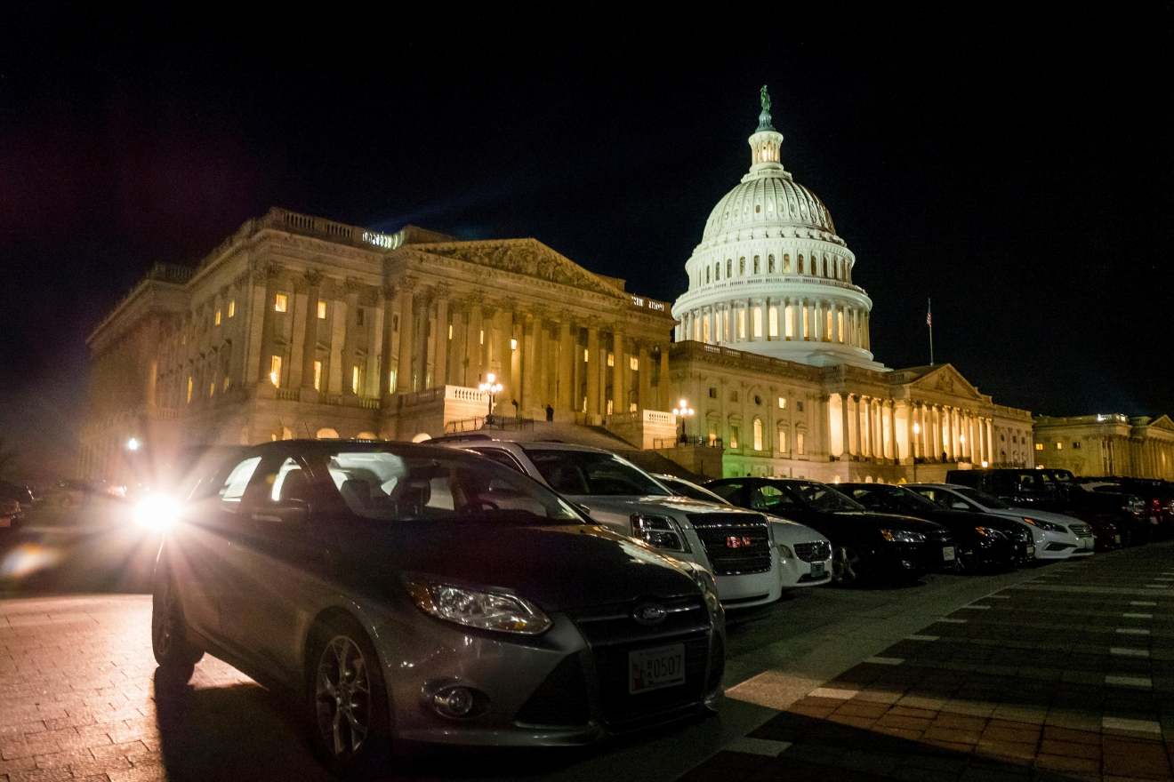 Parked cars surround the U.S. Capitol as the lights burn into the evening on the House of Representives side of the U.S., Capitol on Thursday night, March 23, 2017. (AP Photo/J. David Ake)