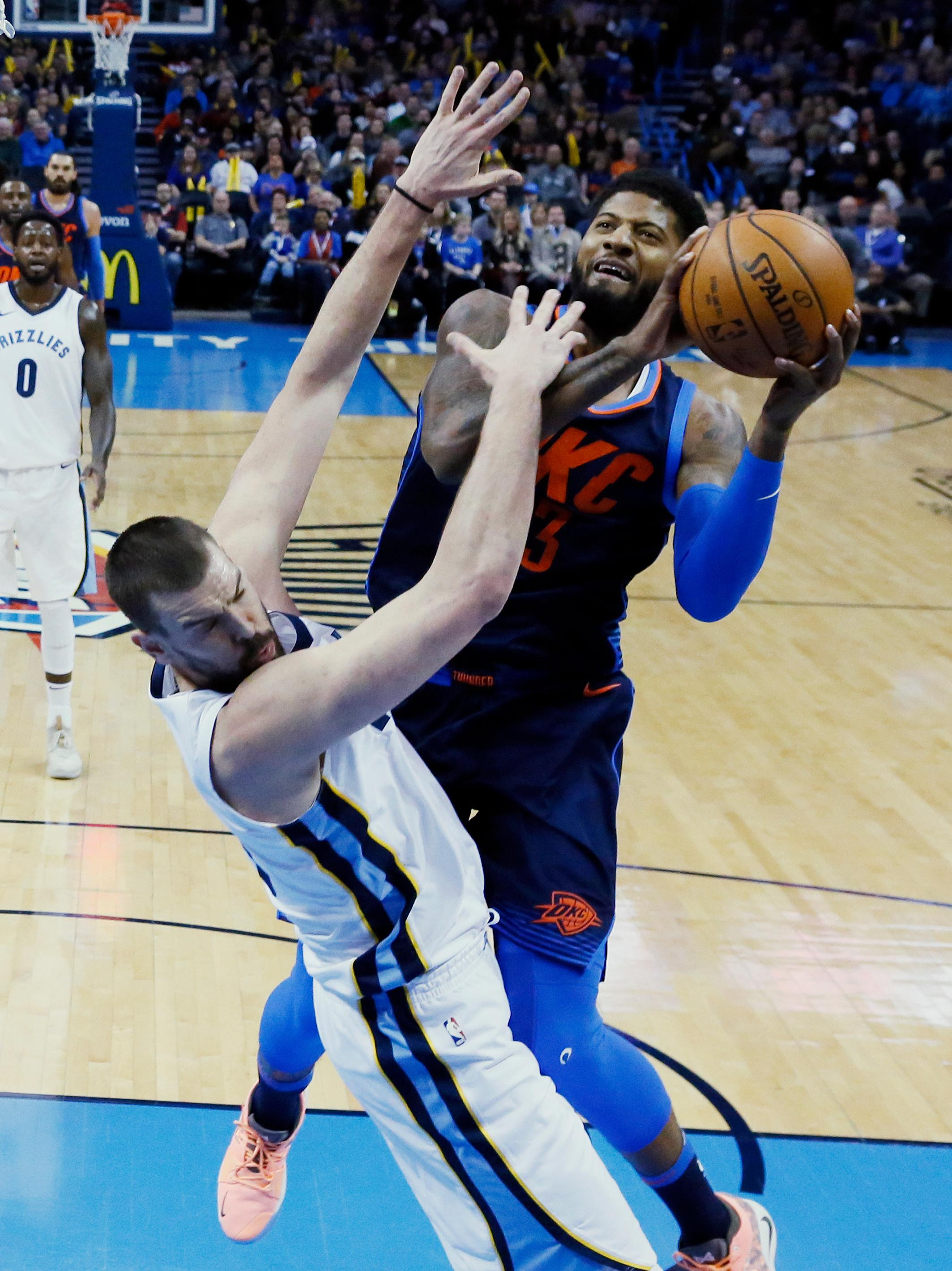 Oklahoma City Thunder forward Paul George, right, shoots her Memphis Grizzlies center Marc Gasol, left, in the first half of an NBA basketball game in Oklahoma City, Sunday, Feb. 11, 2018. (AP Photo/Sue Ogrocki)