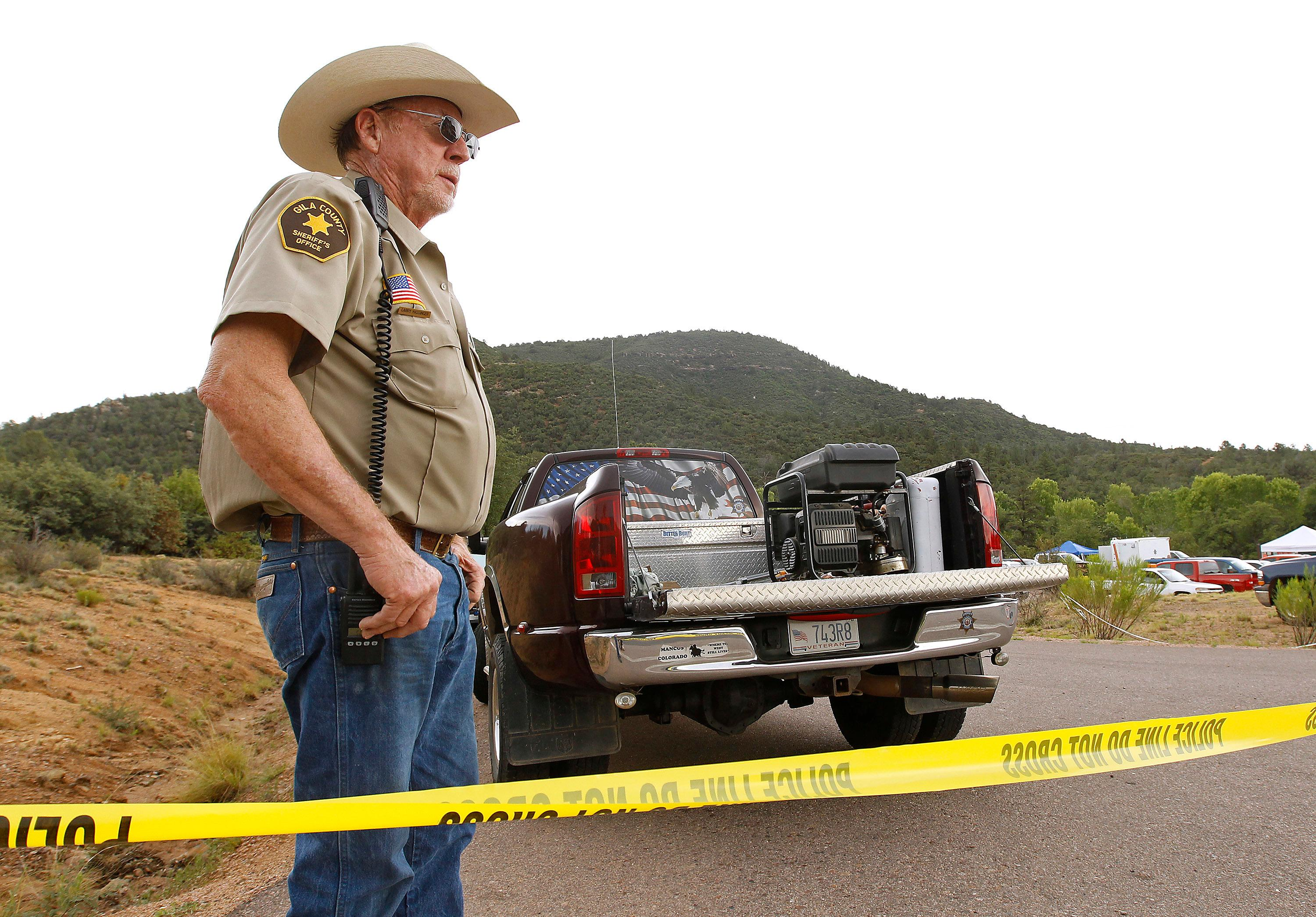 Gila County Sheriff's Office deputy Larry Hassinger stands watch at the entrance to the First Crossing recreation area during a search and rescue operation for victims of a flash flood along the banks of the East Verde River, Sunday, July 16, 2017, in Payson, Ariz. Search and rescue crews, including 40 people on foot and others in a helicopter, have recovered bodies of children and adults, some as far as two miles down the river after Saturday's flash flooding poured over a popular swimming area inside the Tonto National Forest in central Arizona. (AP Photo/Ralph Freso)