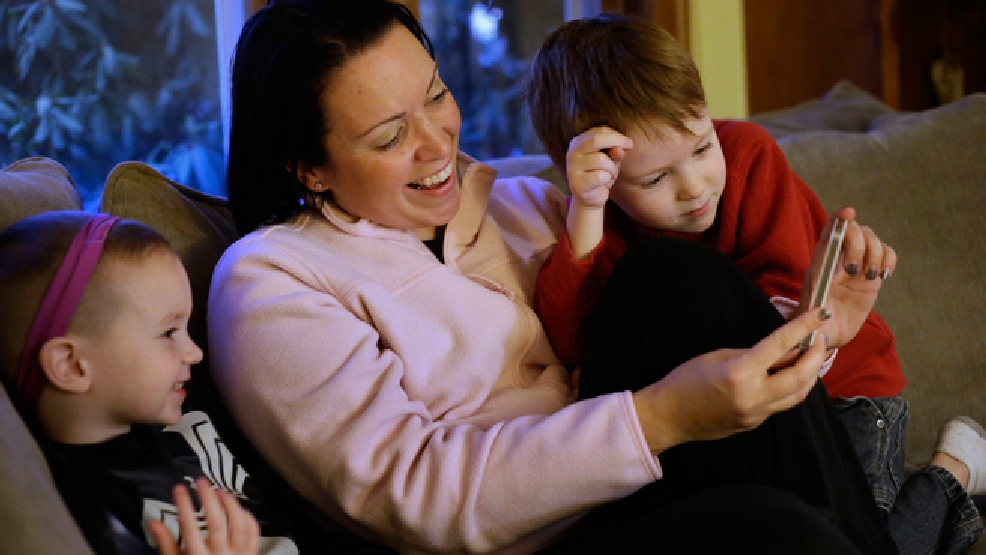 Julie Young, a Boston-based behavioral analyst, center, sits with her sons Nolan, 3, left, and Jameson, 4, right, while looking at a smart phone at their home, in Boston, Monday, Jan. 27, 2014. Child development experts say it's natural for toddlers to be fascinated with their own image, and that interest plays an important developmental role as they develop a sense of self. (AP Photo/Steven Senne)