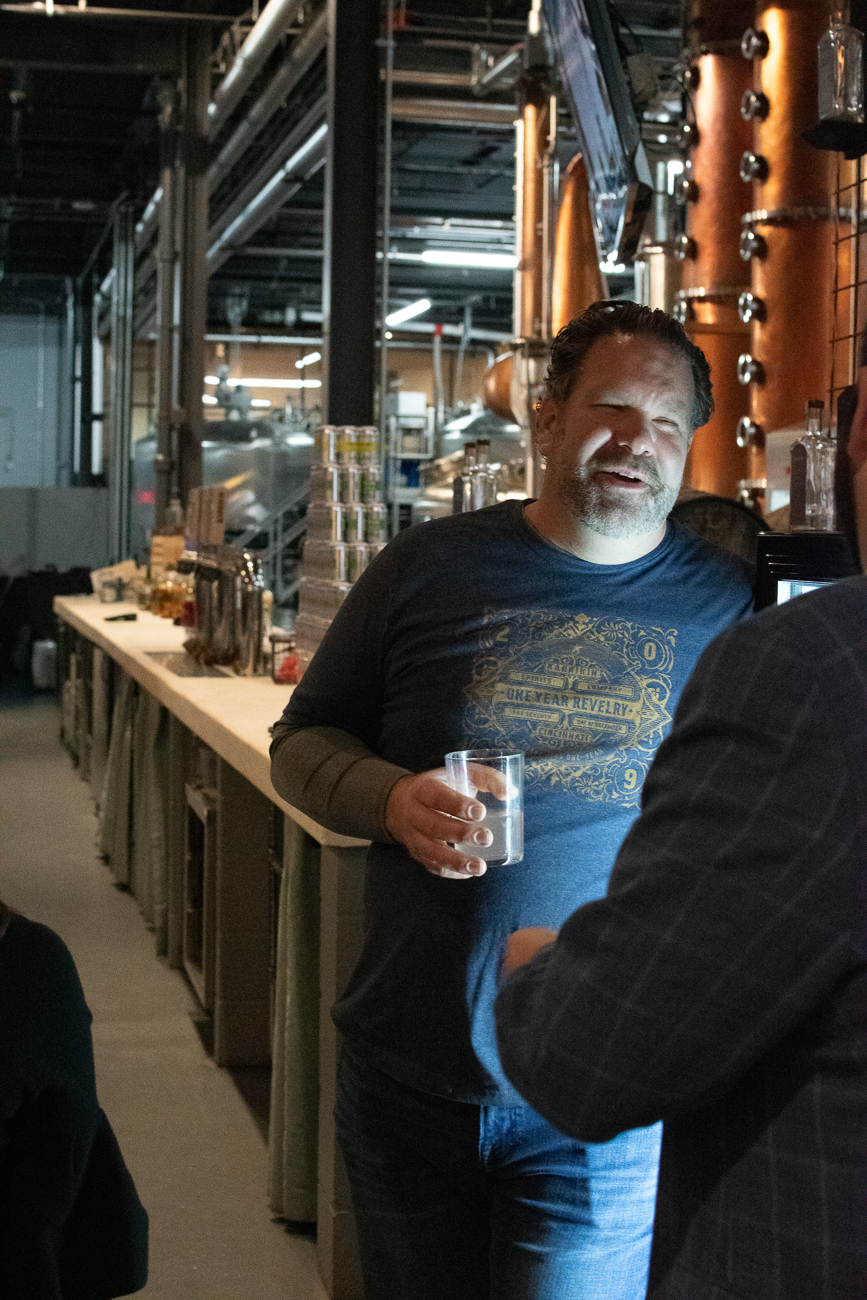 One of Karrikin's seven owners, Jeff Reichard, shares a drink with a guest while donning a special release Revelry tee shirt. / Image: Matt Groves // Published: 12.8.19