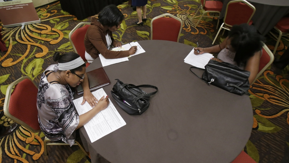 In this Thursday, June 12, 2014 photo, Desirae Gooch, left, fills out an application for a nurse's assistant job, alongside other job seekers filling out applications at the Cleveland Career Fair in Independence, Ohio. (AP Photo/Tony Dejak)