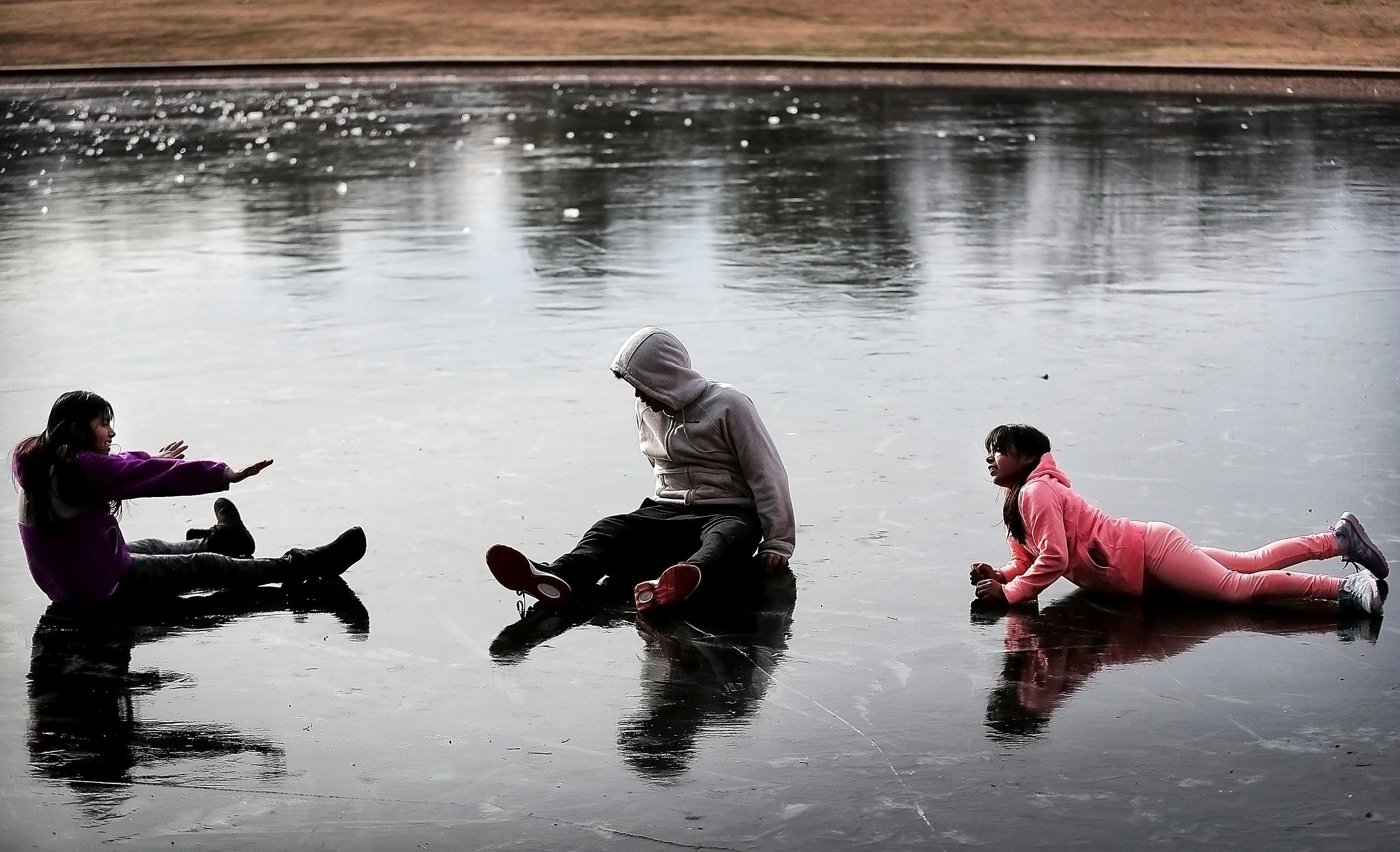 Sherlin Galicia, left, Alexander Galicia, center, and Heidi Galicia play on the iced over pond at Overton Park while walking the dog, Tuesday afternoon, Jan. 2, 2018, in Memphis, Tenn. The isce has grown a couple inches thick on the pond after several nights of sub freezing temperatures, which are expected to continue through the week. (Jim Weber/The Commercial Appeal via AP)