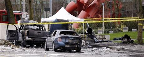 Caution tape surrounds the charred wreckage of a news helicopter and two vehicles after the chopper crashed into a city street near the Space Needle, Tuesday, March 18, 2014, in Seattle.