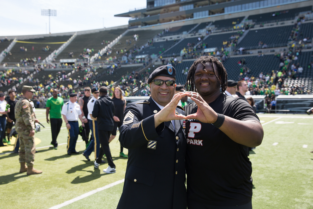 Team Brave defensive lineman Jordon Scott (#34) throws an O with US Army Sergeant First Class Jesus Guzman. The 2017 Oregon Ducks Spring Game provided fans their first look at the team under new Head Coach Willie Taggart's direction.  Team Free defeated Team Brave 34-11 on a sunny day at Autzen Stadium in Eugene, Oregon.  Photo by Austin Hicks, Oregon News Lab