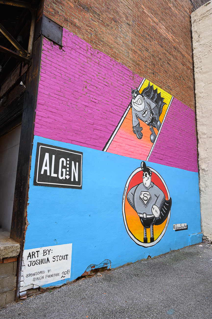 On the back side of Algin Retro (in the alley) are two murals with stylized superheroes: one of Superman, and one of Batman. Both characters are monochrome and surrounded by bright colors and warm gradients. Josh painted each separately. A plan is in place to add a third mural above Batman that will feature Wonder Woman. / Image: Phil Armstrong, Cincinnati Refined // Published: 8.10.19