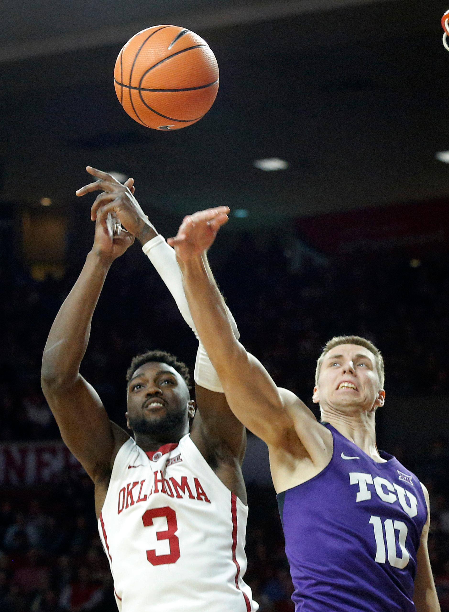 Oklahoma's Khadeem Lattin (3) and TCU's Vladimir Brodziansky (10) fight for the rebound during the first half of an NCAA college basketball game in Norman, Okla., Saturday, Jan. 13, 2018. (AP Photo/Garett Fisbeck)