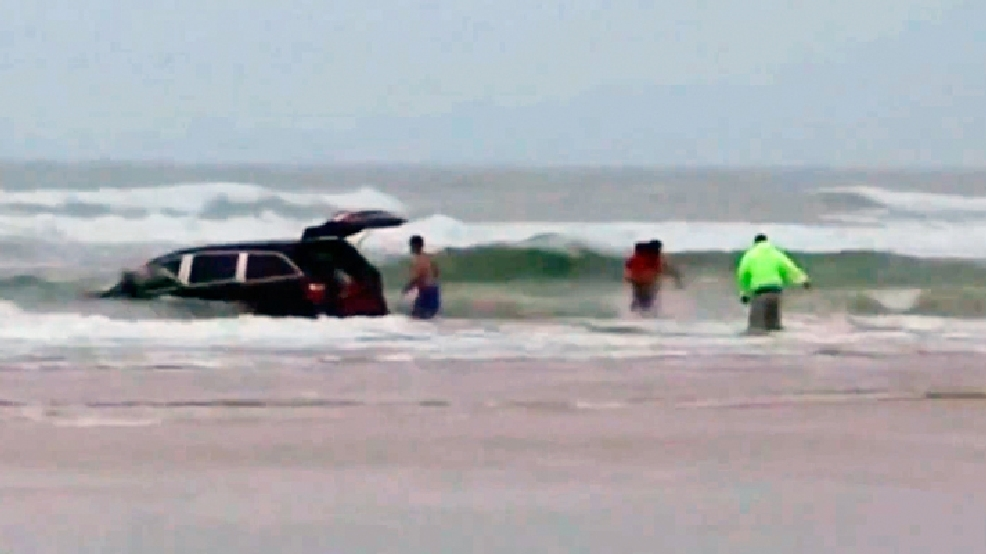 In this image made from video and released by Simon Besner, lifeguards rescue children from a minivan that their mother drove into the Atlantic, Tuesday, March 4, 2014 in Daytona Beach, Fla. (AP Photo/Simon Besner)