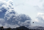 Mount Kelud erupts, as seen from Anyar village in Blitar, East Java, Indonesia, Friday, Feb. 14, 2014. Volcanic ash from the major eruption in Indonesia shrouded a large swath of the country's most densely populated island on Friday, closed three international airports and sent thousands fleeing. (AP Photo/Trisnadi)