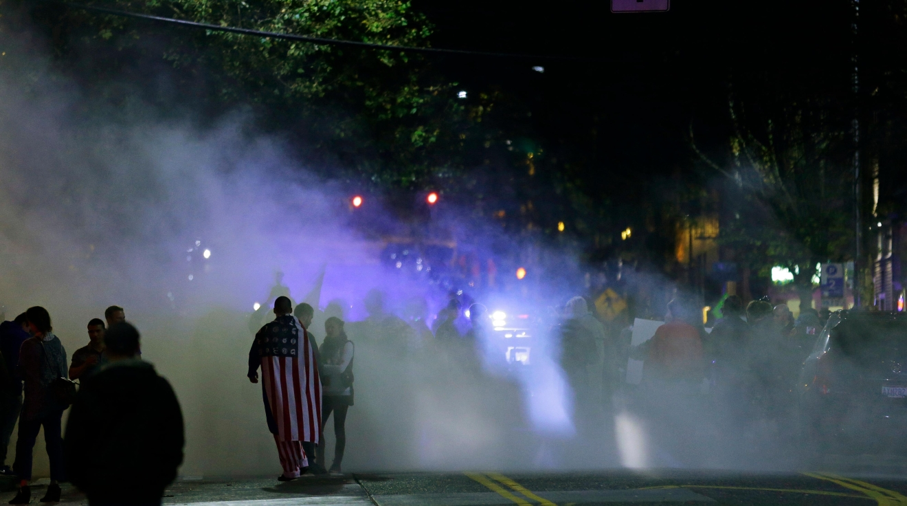 Smoke from a small fire and fire-extinguisher powder rises during a protest against President-elect Donald Trump, Wednesday, Nov. 9, 2016, in Seattle's Capitol Hill neighborhood. (AP Photo/Ted S. Warren)
