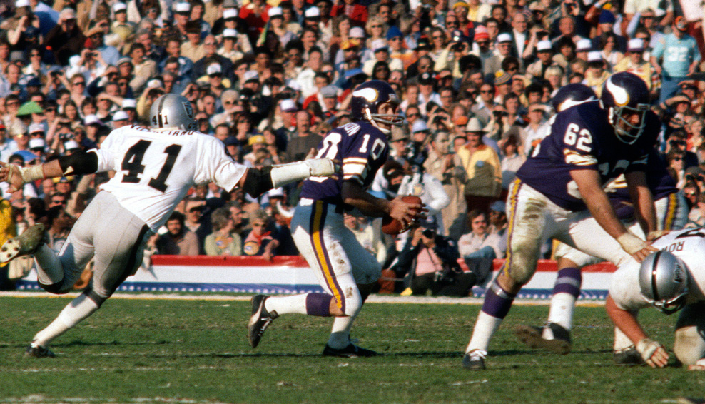 Fran Tarkenton of the Minnesota Vikings scrambles away from the pressure of Phil Villapiano of the Oakland Raiders during Super Bowl XI on Jan. 9, 1977 at the Rose Bowl in Pasadena, Califa. The Raiders won, 32-14. (Photo by Focus on Sport/Getty Images)