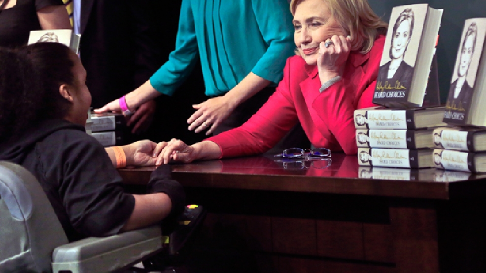 HiIlary Rodham Clinton, right, listens before signing a copy of her new book for a wheelchair-bound woman on Tuesday June 10, 2014, at Barnes and Noble bookstore in New York. (AP Photo/Bebeto Matthews)