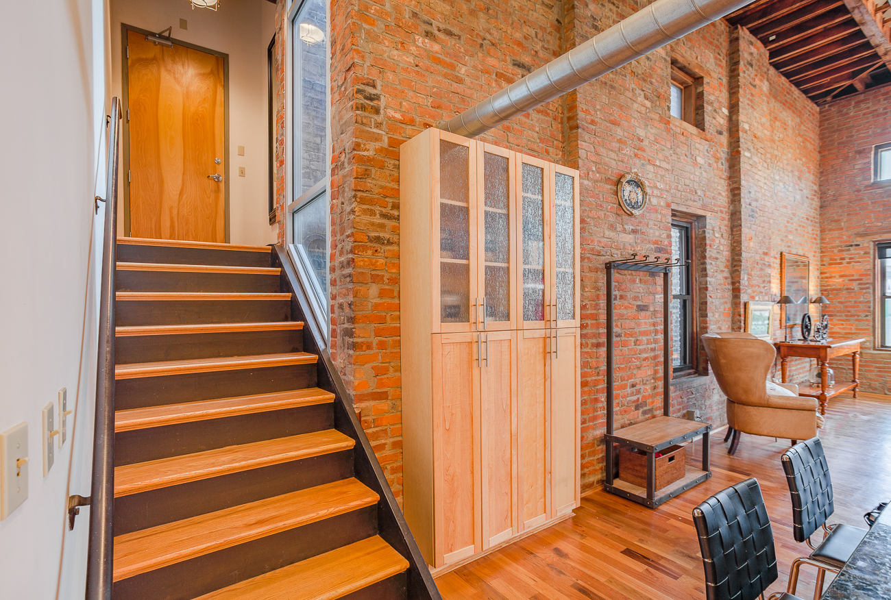 404 Reading Road Unit #401 is a 2-bed, 2-bath condo with a 2-car garage and private rooftop deck in Pendleton. Hardwood flooring and original wooden beams harken back to the building's early days, and plenty of exposed brick enhances the loft's industrial, urban aesthetic. It is listed by Jessa Powers of Huff Realty for $450,000. / Image courtesy of St. Blanc Studios // Published: 3.20.19