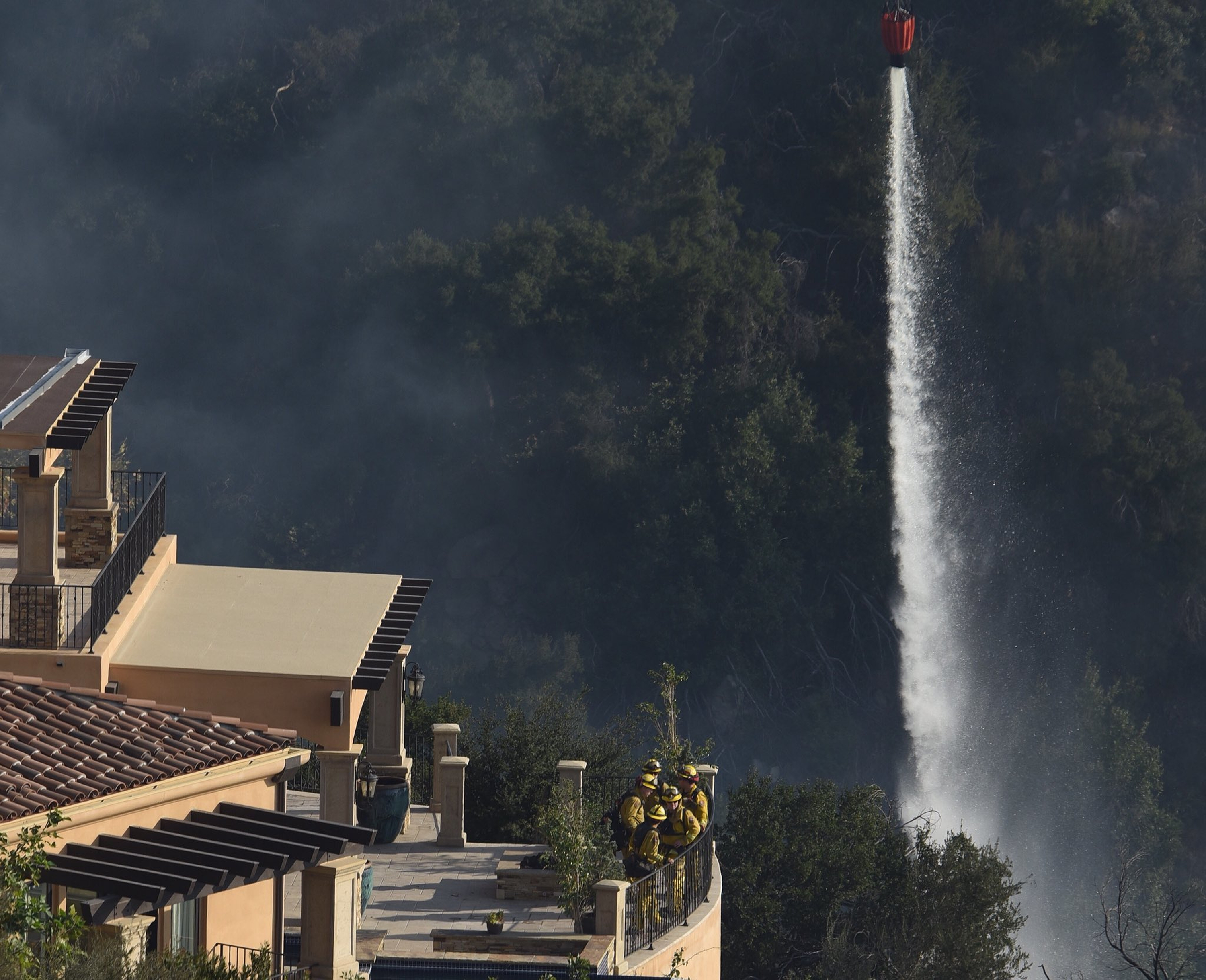 In this photo provided by the Santa Barbara County Fire Department, firefighters standing guard and providing structure protection at a home off Gibraltar Road watch as a bucket full of water is dropped from a helicopter onto a hot spot nearby in Santa Barbara, Calif., Sunday morning, Dec. 17, 2017. The fire has burned more than 700 homes and currently threatens communities in Santa Barbara County. Some 8,000 firefighters are deployed to the so-called Thomas Fire, which has burned for nearly two weeks and still threatens 18,000 homes. (Mike Eliason/Santa Barbara County Fire Department via AP)