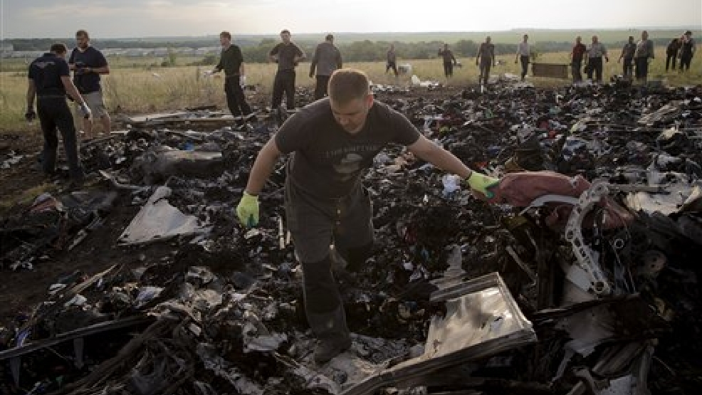 A man looks for the remains of victims in the debris at the crash site of Malaysia Airlines Flight 17 near the village of Hrabove, eastern Ukraine, Saturday, July 19, 2014. World leaders demanded Friday that pro-Russia rebels who control the eastern Ukraine crash site of Malaysia Airlines Flight 17 give immediate, unfettered access to independent investigators to determine who shot down the plane. (AP Photo/Vadim Ghirda)