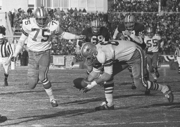 Cowboys defensive end George Andrie, right, picks up a fumble by Bart Starr as teammate Jethro Pugh (75) looks on before running it into the end zone Dec. 31, 1967, during the NFL Championship Game at Lambeau Field. (AP Photo/File)