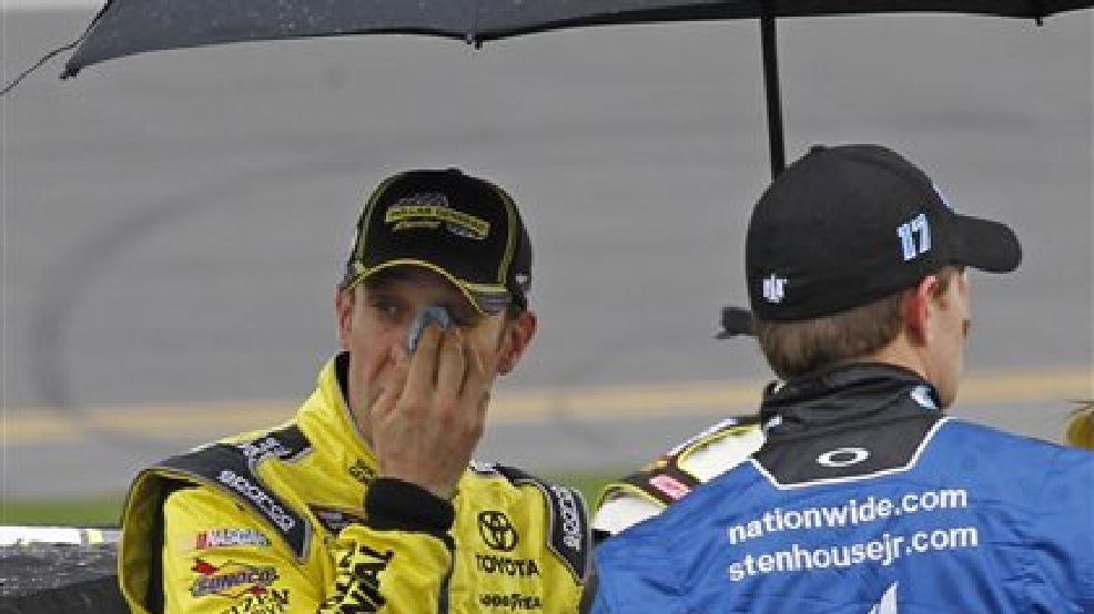 Matt Kenseth, left, looks out from under an umbrella as he stands near his car during a rain delay in the NASCAR Daytona 500 Sprint Cup series auto race at Daytona International Speedway in Daytona Beach, Fla., Sunday, Feb. 23, 2014. (AP Photo/Terry Renna)